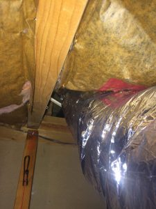 Air conditioning duct going from a knee wall attic to the main attic and leaking like crazy in the process