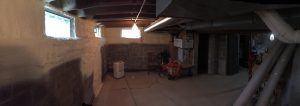 Panoramic view of partially spray foamed basement walls