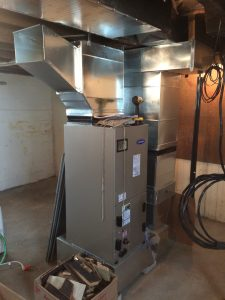 Carrier Green Speed heat pump in the basement with initial duct trunks in place.