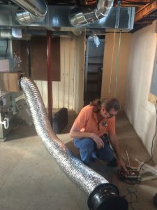 Walter Money setting up his duct blaster to test leakage of the duct system.